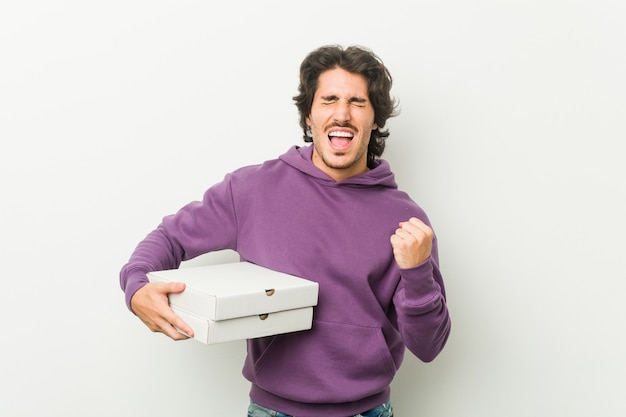 Młody człowiek gospodarstwa pizzy pakiet doping beztroski i podekscytowany