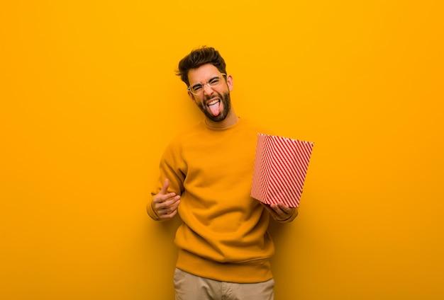 Młody człowiek gospodarstwa popcorns funnny i przyjazny pokazano język