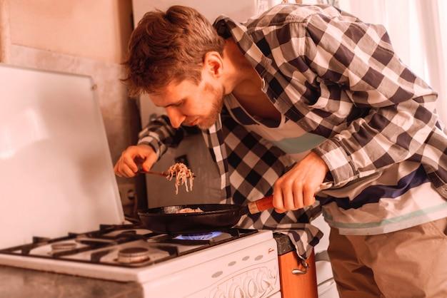 Młody człowiek gotuje zdrowy posiłek na patelni w kuchni, czas wolny podczas przygotowywania posiłków