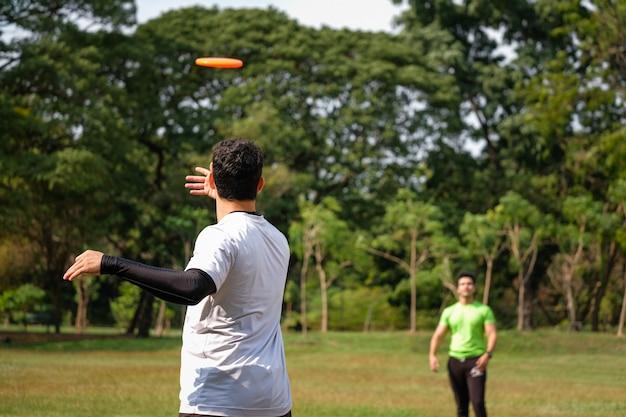 Młody człowiek gra frisbee w parku
