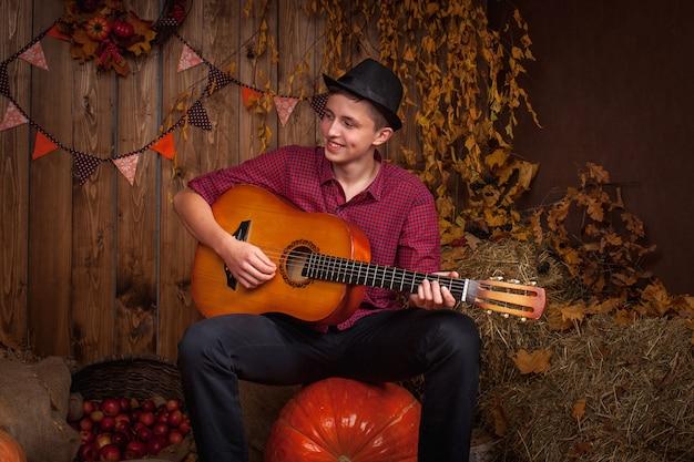 Młody człowiek gra na gitarze i kompozytora jesienią na dyni