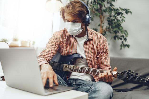 Młody człowiek gra na gitarze w domu w masce medycznej