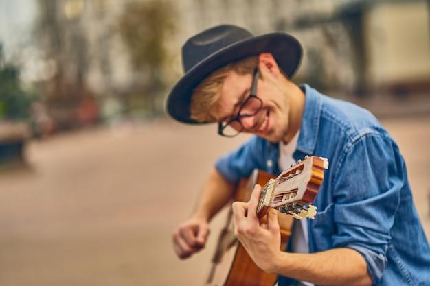 Młody człowiek gra na gitarze