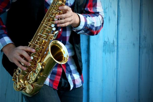Młody człowiek gra na saksofonie na zewnątrz w pobliżu starego muru