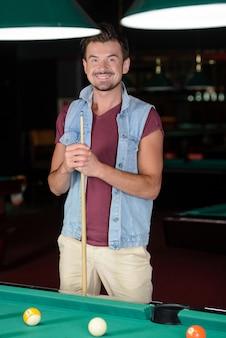 Młody człowiek gra w bilard w ciemnym klubie bilardowym