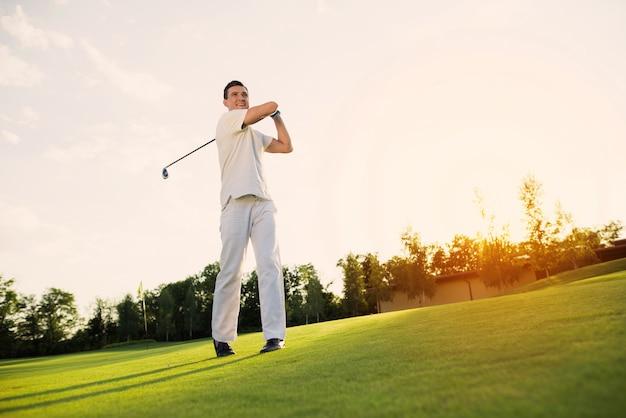 Młody człowiek gra w golfa biorąc huśtawka strzał na trawniku.