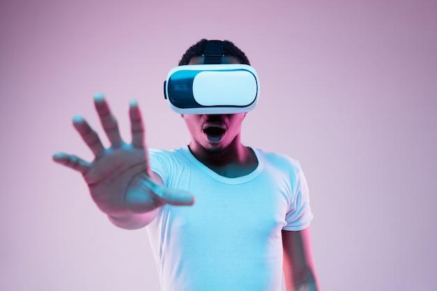 Młody człowiek gra w okularach vr w świetle neonu