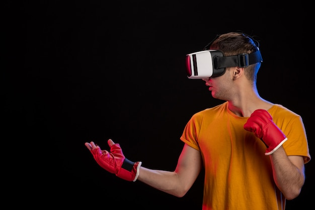 Młody człowiek gra wirtualną rzeczywistość w rękawiczkach mma na czarnej powierzchni