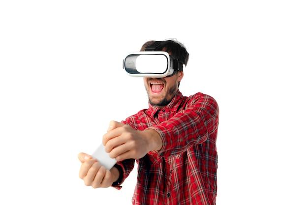 Młody człowiek gra za pomocą zestawu słuchawkowego wirtualnej rzeczywistości na białym tle na ścianie białego studia