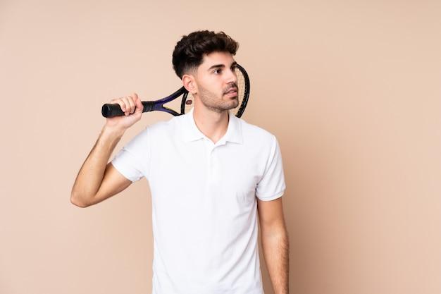 Młody człowiek, grać w tenisa i patrząc w górę
