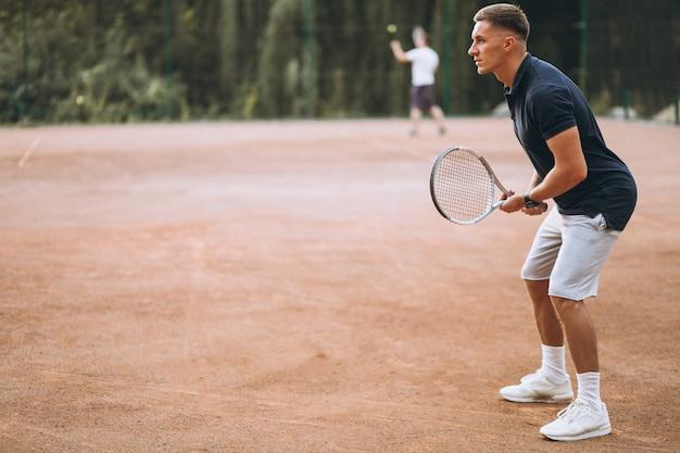 Młody człowiek, grać w tenisa na korcie