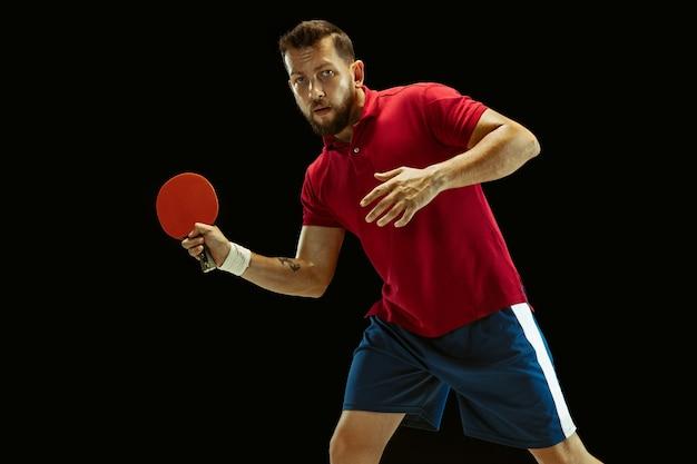 Młody człowiek grać w tenisa stołowego na czarnym studio