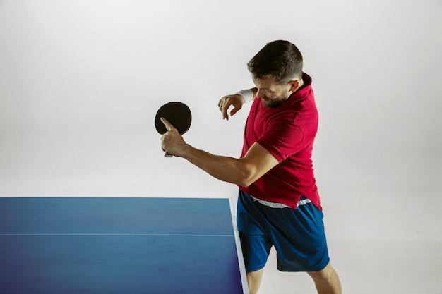 Młody człowiek grać w tenisa stołowego na ścianie białego studia