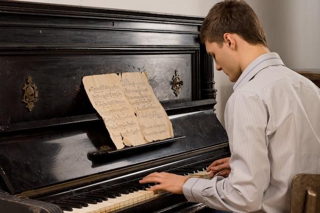 Młody człowiek grający starą nostalgiczną melodię