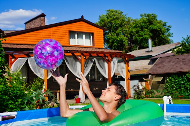 Młody człowiek grający w aktywne gry w basenie rzucający nadmuchiwaną piłkę letnia zabawa i rozrywka ...
