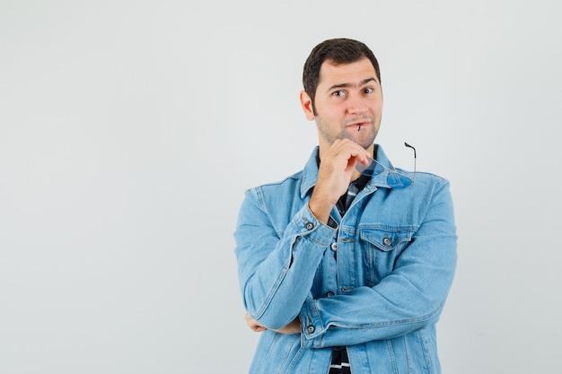 Młody człowiek gryzie okulary myśląc w t-shirt, kurtce i patrząc pewnie.