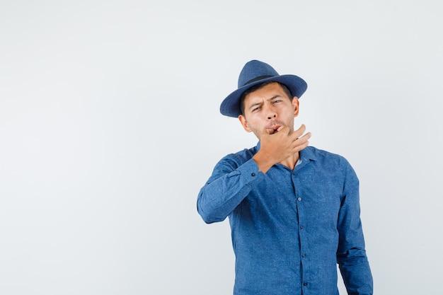 Młody człowiek, gwiżdżąc palcami w niebieską koszulę, kapelusz, widok z przodu.