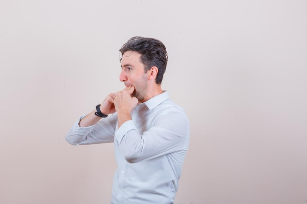 Młody człowiek gwiżdżący palcami w białej koszuli i patrzący optymistycznie
