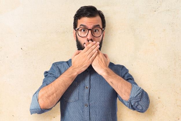 Młody człowiek hipster robi gest niespodzianka