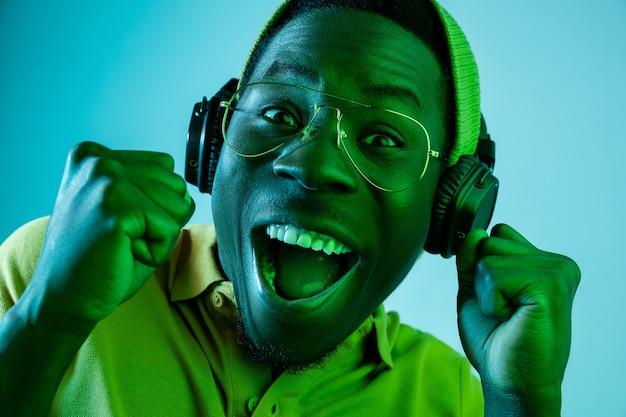 Młody człowiek hipster słuchanie muzyki w słuchawkach w niebieskim studio z neonów. ekspresja emocjonalna