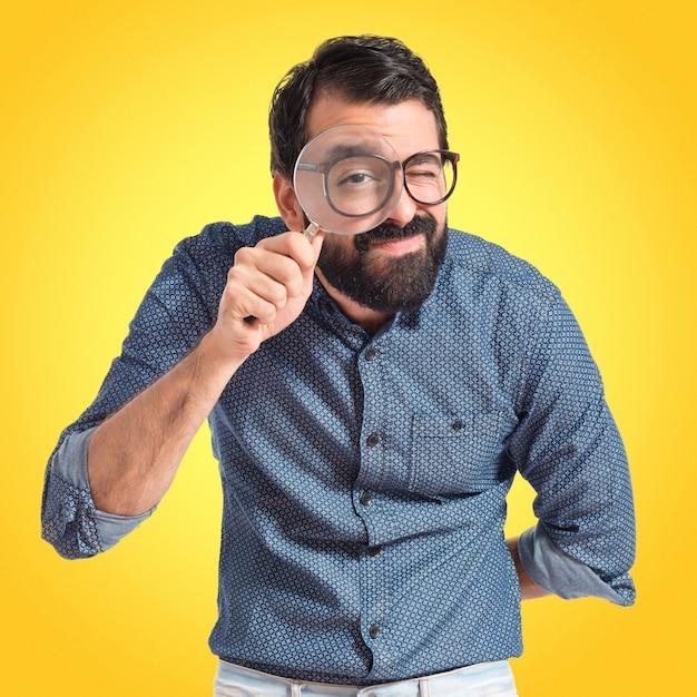 Młody człowiek hipster z lupą na kolorowe tło