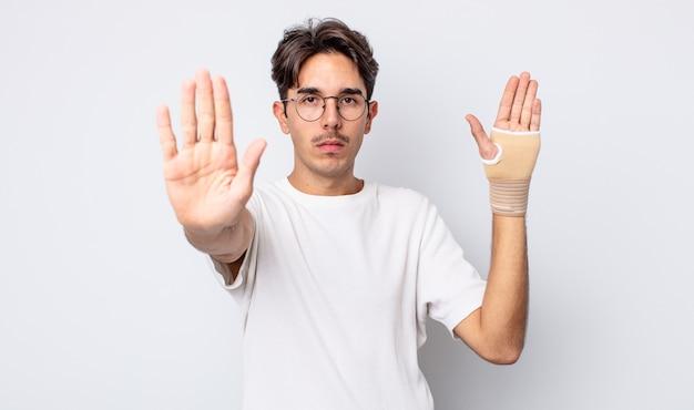 Młody człowiek hispanic patrząc poważne pokazując otwartą dłoń co gest zatrzymania. koncepcja bandaża ręcznego