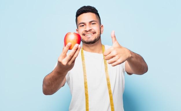 Młody człowiek hispanic szczęśliwy wyrażenie i trzyma jabłko. koncepcja diety