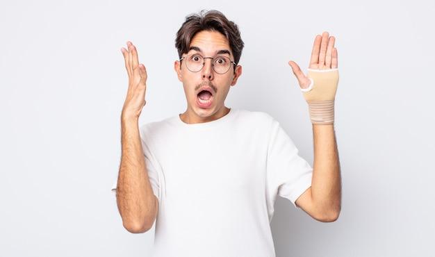 Młody człowiek hiszpanin krzyczy z rękami w powietrzu. koncepcja bandaża ręcznego
