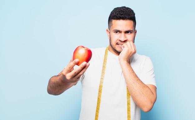 Młody człowiek hiszpanin przestraszony wyrażenie i trzyma jabłko. koncepcja diety