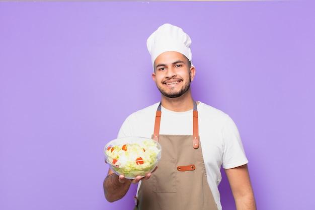 Młody człowiek hiszpanin szczęśliwy wypowiedzi. szef kuchni z koncepcją sałatki