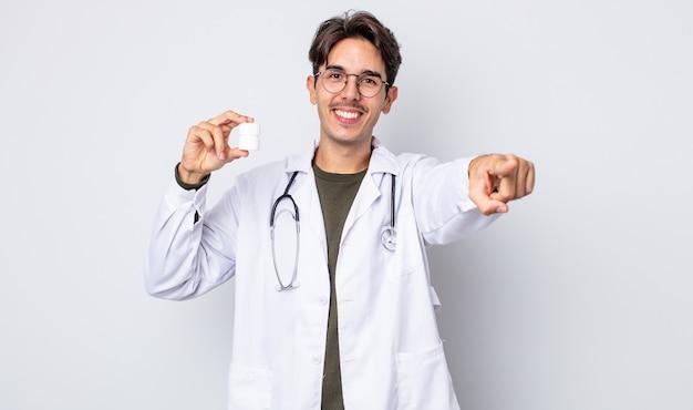 Młody człowiek hiszpanin, wskazując na aparat wybierając ciebie. lekarz z koncepcją butelki tabletek