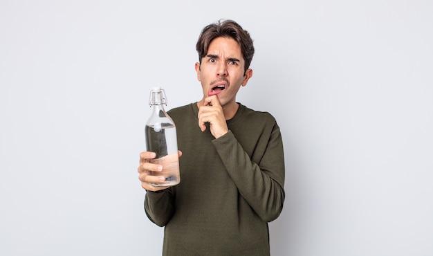 Młody człowiek hiszpanin z szeroko otwartymi ustami i oczami i ręką na brodzie. koncepcja butelki z wodą