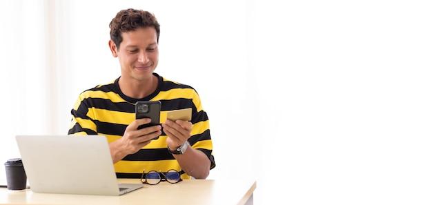 Młody człowiek hiszpanin za pomocą karty kredytowej do płatności online za pomocą smartfona i laptopa w domu lub w biurze kreatywnym miejscu pracy.