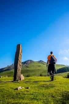 Młody człowiek idący obok prehistorycznego dolmana na szczycie monte adarra w urniecie, niedaleko san sebastian. gipuzkoa, kraj basków, zdjęcie pionowe