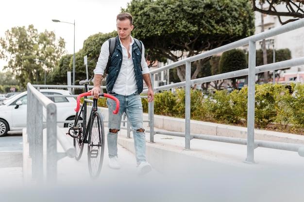 Młody człowiek idący obok swojego roweru
