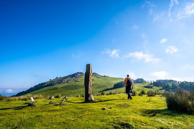 Młody człowiek idący prehistorycznym dolmenem na szczycie góry adarra w urniecie, niedaleko san sebastian. gipuzkoa, kraj basków