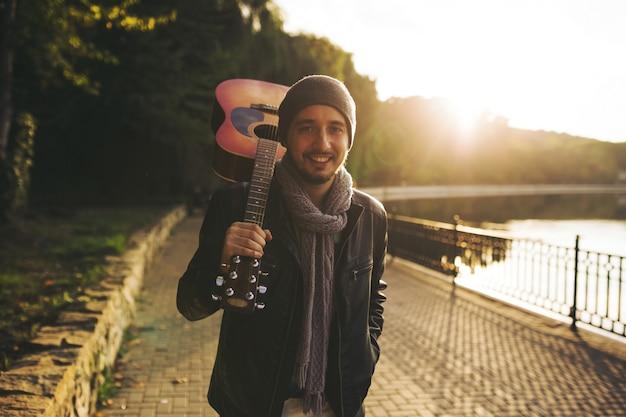 Młody człowiek idzie nad jeziorem i trzyma gitarę