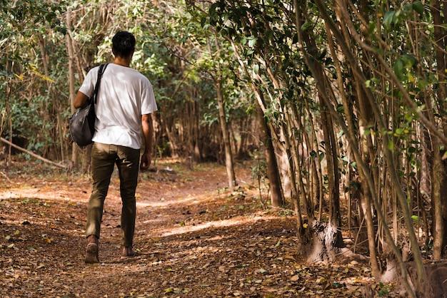 Młody człowiek idzie w lesie