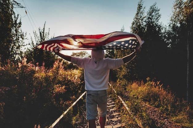 Młody człowiek idzie wzdłuż torów kolejowych drogi z amerykańską flagą w kierunku zachodu słońca. mężczyzna stoi na opuszczonej drodze z szynami na obszarze wiejskim z flagą w paski i gwiazdy. pojęcie podróży, wolność