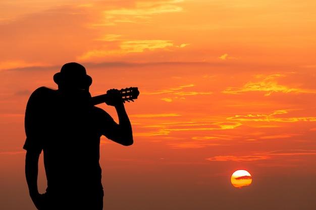 Młody człowiek idzie wzdłuż torów w świetle zachodu słońca.
