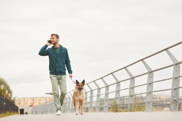 Młody człowiek idzie z psem po ulicy i rozmawia przez telefon komórkowy