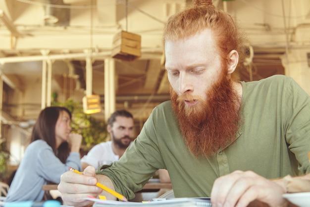Młody człowiek imbir za pomocą tabletu w kawiarni