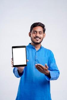 Młody człowiek indian wyświetlono tabletki na białym tle.