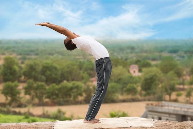 Młody człowiek indyjski na szczycie góry siedzącej w pozie jogi.