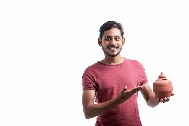 Młody człowiek indyjski trzyma w ręku gliny skarbonka na białym tle.