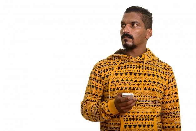 Młody człowiek indyjski trzymając telefon komórkowy myśląc na białym tle