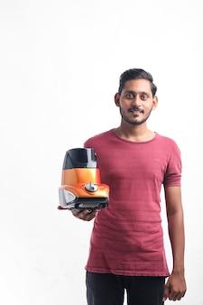 Młody człowiek indyjski trzymając w ręku mikser elektroniczny na białym tle.