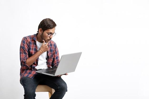 Młody człowiek indyjski za pomocą laptopa i dając zaskoczony wyraz