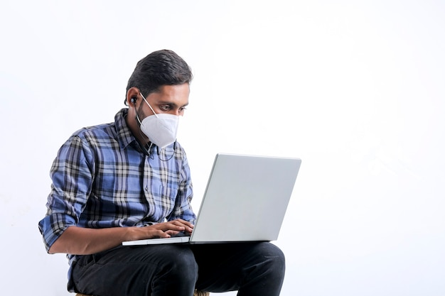 Młody człowiek indyjski za pomocą laptopa na białym tle.