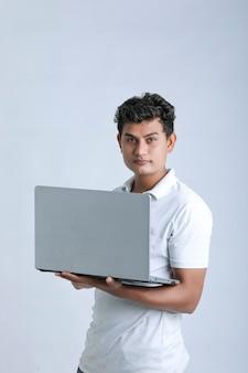 Młody człowiek indyjski za pomocą laptopa.